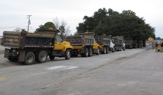 A long line of South Carolina Department of Transportation dump trucks wait to be filled with sand on Monday, Feb. 10, 2014, in Columbia, S.C. The DOT and others are preparing for the state's second winter storm in as many weeks. Forecasters say this storm systemcould include an ice storm. (AP Photo/Jeffrey Collins)