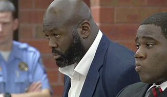 FILE - In this Oct. 21, 2013 file photo from video, former NFL defensive end and ex-ESPN analyst Hugh Douglas, center, stands with his attorney, Corey Brinson, right, during his arraignment in Superior Court in Hartford, Conn. Douglas is expected to plead no contest to a misdemeanor to resolve a case that accused him of assaulting his girlfriend at a Hartford hotel, his lawyer said Friday, Feb. 7, 2014. (AP Photo/WFSB-TV, Peter McCue, Pool File)