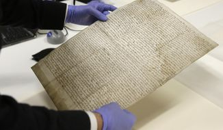 In this Wednesday, Feb. 5, 2014 photo, Chris Woods, director of London's National Conservation Service, very carefully handles the Magna Carta, in Houston. The centuries old parchment will be on display at the Houston Museum of Natural Science for six months starting Feb. 14, 2014. (AP Photo/Pat Sullivan)