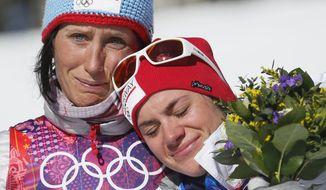 Norway's gold medal winner Marit Bjoergen, left, hugs bronze medal winner Heidi Weng during the flower ceremony of the women's cross-country 15k skiathlon at the 2014 Winter Olympics, Saturday, Feb. 8, 2014, in Krasnaya Polyana, Russia. (AP Photo/Dmitry Lovetsky)
