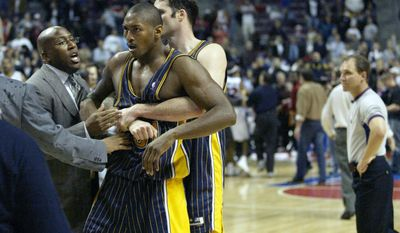 FILE - In this Nov. 19, 2004 file photo, Indiana Pacers' Ron Artest is restrained before being escorted off the court following a fight with the Detroit Pistons and fans in Auburn Hills, Mich. Artest, now known as Metta World Peace and with the New York Knicks, believes Marcus Smart can learn from the fallout that will come after the Oklahoma State All-American shoved a fan during an NCAA college basketball game at Texas Tech on Saturday, Feb. 8, 2014. Smart was suspended three games by the Big 12 on Sunday. (AP Photo/Duane Burleson, File)