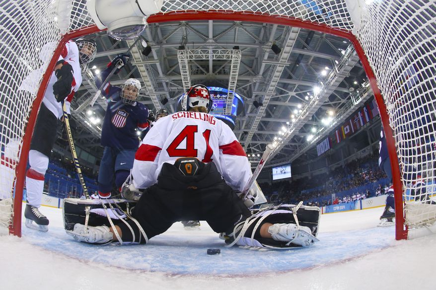 Hilary Knight of the Untied States celebrates as the puck slides past Goalkeeper Florence Schelling of Switzerland for a goal during the first period of the women's ice hockey game at the 2014 Winter Olympics, Monday, Feb. 10, 2014, in Sochi, Russia. (AP Photo/Bruce Bennett, Pool)