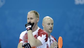 Canada's skip, Brad Jacobs, left, and Ryan Fry, right, wait for their turn to curl during the men's curling competition against Germany at the 2014 Winter Olympics, Monday, Feb. 10, 2014, in Sochi, Russia. (AP Photo/Wong Maye-E)