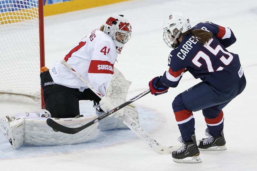 Alex Carpenter of the Untied States scores a goal against Goalkeeper Florence Schelling of Switzerland during the third period of the 2014 Winter Olympics women's ice hockey game at Shayba Arena, Monday, Feb. 10, 2014, in Sochi, Russia. USA defeated Switzerland 9-0. (AP Photo/Petr David Josek)