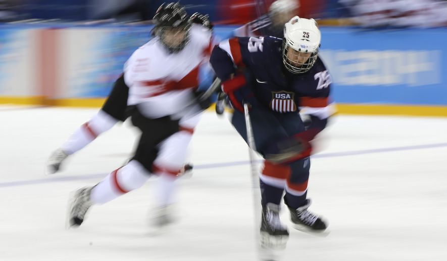 Alex Carpenter of the Untied States controls the puck as Sarah Forster of Switzerland closes in during the third period of the 2014 Winter Olympics women's ice hockey game at Shayba Arena, Monday, Feb. 10, 2014, in Sochi, Russia. (AP Photo/Matt Slocum)
