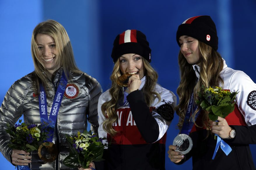 Canada's Justine Dufour-Lapointe, center, bites her gold medal while flanked by bronze medalist Hannah Kearney of the United States, left, and her sister silver medalist Chloe Dufour-Lapointe during their medals ceremony for the women's moguls at the 2014 Winter Olympics, Sunday, Feb. 9, 2014, in Sochi, Russia. (AP Photo/Morry Gash)