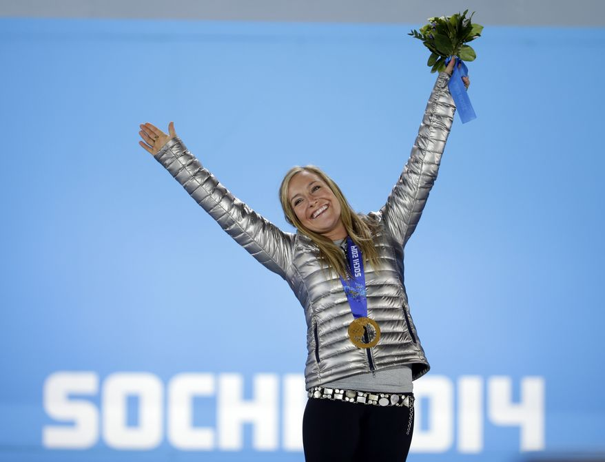 Women's snowboard slopestyle gold medalist Jamie Anderson of the United States stands on the podium during the medals ceremony at the 2014 Winter Olympics, Sunday, Feb. 9, 2014, in Sochi, Russia. (AP Photo/David Goldman)