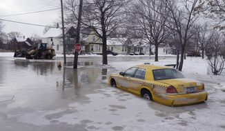 A taxi cab is surrounded by water on a flooded street after a water main break in Detroit on Tuesday, Feb. 11, 2014. The broken water main flooded a several-block area in southwest Detroit, trapping several cars. (AP Photo/Carlos Osorio)