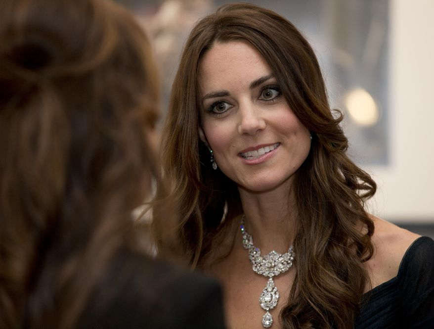 Kate Duchess of Cambridge talks to guests at a fund raising gala at the National Portrait Gallery in London, Tuesday, Feb. 11, 2014. . The Duchess is wearing a dress by British designer Jenny Packham and a necklace on loan from Queen Elizabeth II that was given to the Queen as a gift for her wedding in 1947. (AP Photo/Alastair Grant, Pool)