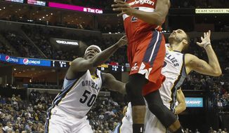 Washington Wizards guard John Wall (2) goes to the basket against Memphis Grizzlies forward Zach Randolph (50) and guard Nick Calathes, right, in the first half of an NBA basketball game, Tuesday, Feb. 11, 2014, in Memphis, Tenn. (AP Photo/Lance Murphey)