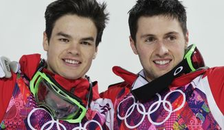 Canada's Alex Bilodeau, right,  celebrates with compatriot Mikael Kingsbury after Bilodeau won gold and Kingsbury took silver in the men's moguls final at the 2014 Winter Olympics, Monday, Feb. 10, 2014, in Krasnaya Polyana, Russia.  (AP Photo/Andy Wong)