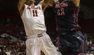 Alabama forward Shannon Hale, left, shoots over Mississippi forward Sebastian Saiz during an NCAA college basketball game Tuesday, Feb. 11, 2014, at Coleman Coliseum in Tuscaloosa, Ala. (AP Photo/AL.com, Vasha Hunt) MAGS OUT