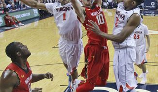 Virginia guard Justin Anderson (1) and Virginia forward Darion Atkins, right, combine to block a shot by Maryland forward Jake Layman (10) during the second half of an NCAA college basketball game in Charlottesville, Va., Monday, Feb. 10, 2014. Virginia won the game 61-53.   (AP Photo/Steve Helber)