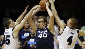 Xavier center Matt Stainbrook (40) is trapped by Butler forwards Andrew Chrabascz, left, and Erik Fromm (4) in the first half of an NCAA college basketball game in Indianapolis, Tuesday, Feb. 11, 2014. (AP Photo/Michael Conroy)