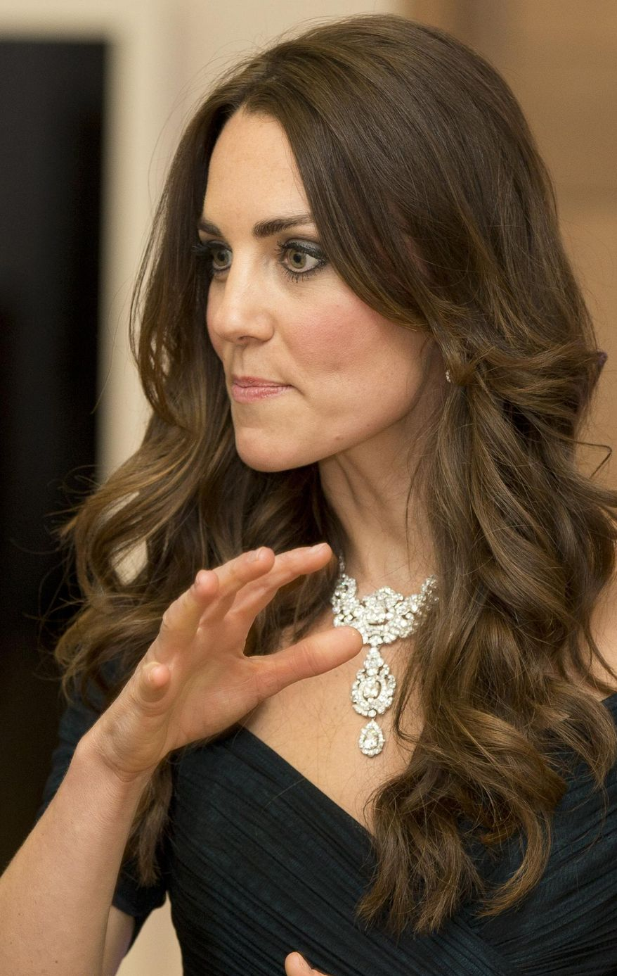 Kate Duchess of Cambridge talks to guests at a fund raising gala at theNational Portrait Gallery in London, Tuesday, Feb. 11, 2014. . The Duchess is wearing a dress by British designer Jenny Packham and a necklace on loan from Queen Elizabeth II that was given to the Queen as a gift for her wedding in 1947. (AP Photo/Alastair Grant, Pool)