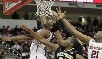 North Carolina State's  T.J. Warren drives under the basket as Wake Forest's Travis McKie (30) and North Carolina State's Beejay Anya (21) reach for the ball during the first half of an NCAA college basketball game in Raleigh, N.C., Tuesday, Feb. 11, 2014. (AP Photo/Gerry Broome)