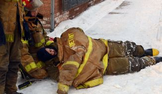 An injured firefighter, who was hurt while battling a blaze in an abandoned commercial building on Detroit's eastside, right, lies on the ground next to colleagues, Tuesday, Feb. 11, 2014. Battalion Chief Richard Wright says the firefighter fell at least 10 feet from an aerial lift to ground after being hit by flying bricks. (AP Photo/Bill Eisner)