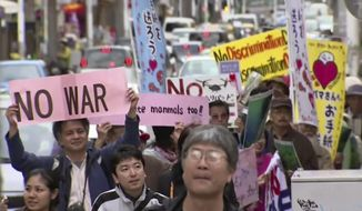 In this video image taken from AP video, protesters march against the relocation plan of the US base in Naha, OKinawa prefecture, Feb. 11, 2014.  Several hundred people rallied Tuesday against a contentious plan to relocate a U.S. military base to another site on Okinawa ahead of U.S. Ambassador Caroline Kennedy's visit to the southern Japanese island. (AP Photo via AP video)