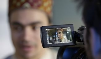 India's Shiva Keshavan is interviewed after speaking at a luncheon at the 2014 Winter Olympics, Tuesday, Feb. 11, 2014, in Sochi, Russia. Keshavan competed in the men's singles luge under the Olympic flag because India's Olympic body had been suspended by the IOC in 2012 over a corruption scandal. The IOC executive board reinstated the Indian Olympic body on Tuesday, Feb. 11, 2014, after it held a weekend ballot that complied with ethics rules barring corruption-tainted officials from running for election. (AP Photo/Morry Gash)