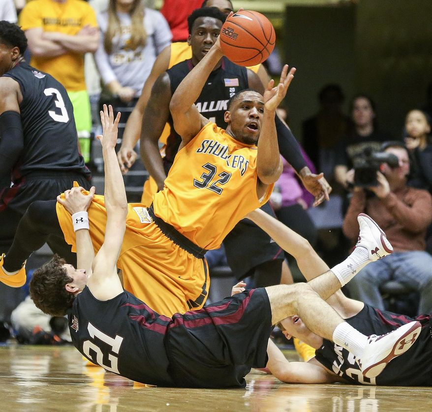 Wichita State's Tekele Cotton dishes the ball off after winning a loose ball against Southern Illinois' Tyler Smithpeters during the first half of an NCAA college basketball game Tuesday, Feb. 11, 2014, in Wichita, Kan. (AP Photo/The Wichita Eagle, Fernando Salazar) LOCAL TV OUT; MAGS OUT LOCAL RADIO OUT; LOCAL INTERNET OUT