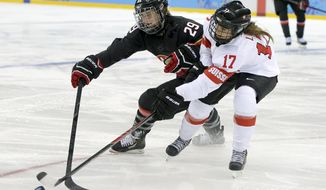 Marie-Philip Poulin of Canada and Jessica Lutz of Switzerland battle for control of the puck during the second period of the women's ice hockey game at the Shayba Arena during the 2014 Winter Olympics, Saturday, Feb. 8, 2014, in Sochi, Russia. (AP Photo/Matt Slocum)