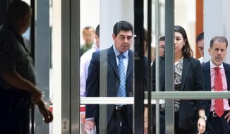 FILE - In this May 24, 2013, file photo, former Cameron County District Attorney Armando Villalobos, center,  exits the federal courthouse in Brownsville, Texas, after a jury found him guilty on seven counts that include racketeering, bribery and extortion. Villalobos was scheduled to be sentenced on Tuesday, Feb. 11, 2014. He was among a dozen people swept up in a FBI investigation that began with former state District Judge Abel Limas.  (AP Photo/The Brownsville Herald, Paul Chouy, File) MAGS OUT; TV OUT; MANDATORY CREDIT