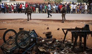 "People gather to watch French soldiers search a house used as an armed cache in the Christian sector of PK12, the last checkpoint at the exit of the town, in Bangui, Central African Republic Tuesday Feb. 11, 2014. The commander of French troops in the Central African Republic General Francisco Soriano accused the Anti-Balaka Christian militias to be ""enemies of the peace"" and should be dealt with accordingly. (AP Photo/Jerome Delay)"