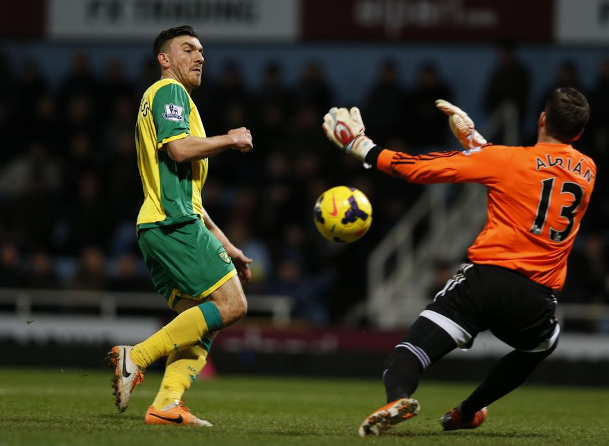West Ham United's goalkeeper Adrian, right, stops a goal attempt shot from Norwich City's Robert Snodgrass during their English Premier League soccer match at Upton Park, London, Tuesday, Feb. 11, 2014. (AP Photo/Sang Tan)