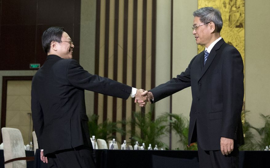 Wang Yu-chi, front left, head of Taiwan's Mainland Affairs Council, shakes hands with Zhang Zhijun, front right, director of China's Taiwan Affairs Office, before their meeting in Nanjing, in eastern China's Jiangsu Province, Tuesday, Feb. 11, 2014. Taiwan and China are holding their highest-level talks since splitting amid a civil war 65 years ago, hoping to further boost contacts and ease lingering tensions, even as political developments on the self-governing island swing away from Beijing's goal of eventual unification. (AP Photo/Alexander F. Yuan)