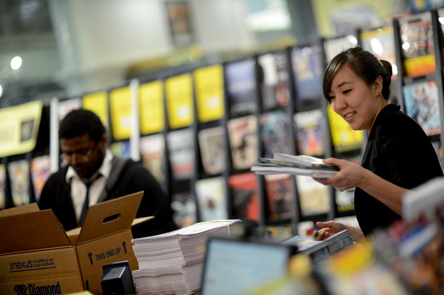 Esther Kim, manager at Fantom Comics and Chris Scott, left, unload new comic books at their store in Union Station, Washington, D.C., Tuesday, February 11, 2014. (Andrew Harnik/The Washington Times)