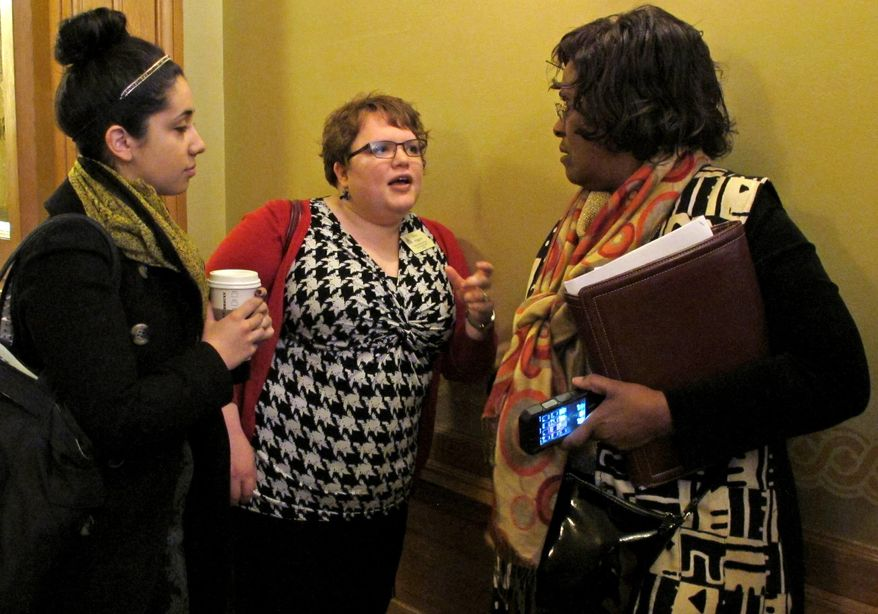 Ariana Nasrazadani, left, an intern for Planned Parenthood of Kansas and Mid-Missouri, and Elise Higgins, center, a Planned Parenthood lobbyist, confer with Kansas state Rep. Valdenia Winn, right, a Kansas City Democrat, following a legislative committee meeting on abortion legislation, Tuesday, Feb. 11, 2014, at the Statehouse in Topeka, Kan. Planned Parenthood is officially neutral on a bill making technical changes in anti-abortion laws. (AP Photo/John Hanna)