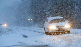 Vehicles slowly make their way on a snow-covered Alabama state Route 35, on Tuesday, Feb. 11, 2014, in Fort Payne, Ala. Residents woke to a blanket of snow that was expected to continue throughout the morning hours. (AP Photo/Hal Yeager)