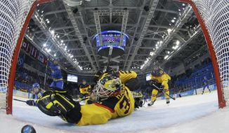Goalkeeper Jennifer Harss of Germany reaches for the puck as Johanna Olofsson's of Sweden shot get by her for a goal during the third period of women's ice game at Shayba Arean during the 2014 Winter Olympics, Tuesday, Feb. 11, 2014, in Sochi, Russia. (AP Photo/Mark Blinch, Pool)