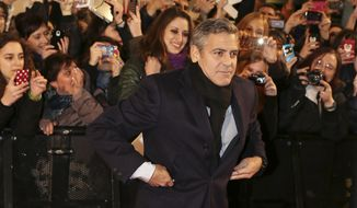 "American actor George Clooney poses for photographers on the red carpet for the screening of the movie ""Monuments Men "", in Pioltello, near Milan, Italy, Monday, Feb. 10, 2014. (AP Photo/Antonio Calanni)"