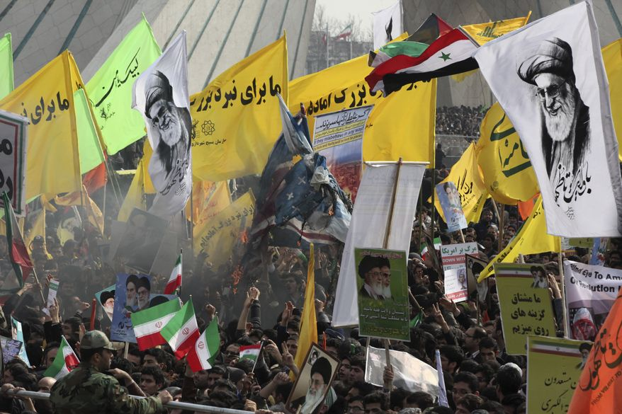 """Iranians burn representations of British, Israeli, and U.S. flags, as they hold pro-government placards and portraits of supreme leader Ayatollah Ali Khamenei during an annual rally commemorating anniversary of the 1979 Islamic revolution, at the Azadi, 'Freedom' Square in Tehran, Iran, Tuesday, Feb. 11, 2014. Tuesday marks the 35th anniversary of the revolution that toppled the pro-U.S. Shah Mohammad Reza Pahlavi and brought Islamists to power. The banners in yellow read, """"we are ready for the great battle."""" (AP Photo/Vahid Salemi)"""