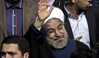 """Escorted by his bodyguards, Iranian President Hassan Rouhani, center, waves to his well wishers as he attends an annual rally commemorating the anniversary of the 1979 Islamic revolution, in Tehran, Iran, Tuesday, Feb. 11, 2014. Rouhani on Tuesday called for """"fair and constructive"""" nuclear talks with world powers as the nation marked the anniversary of the 1979 Islamic revolution with massive rallies, complete with anti-American and anti-Israeli chants. Tuesday marks the 35th anniversary of the revolution that toppled the pro-U.S. Shah Mohammad Reza Pahlavi and brought Islamists to power. Hossein, brother of the President Rouhani accompanies him at right. (AP Photo/Vahid Salemi)"""