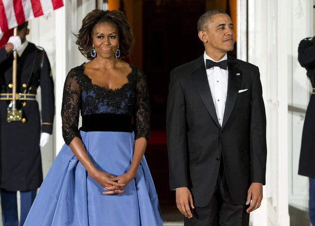 First lady Michelle Obama, left, and President Barack Obama wait for the arrival of French President François Hollande for a State Dinner at the North Portico of the White House on Tuesday, Feb. 11, 2014, in Washington. (AP Photo/ Evan Vucci)