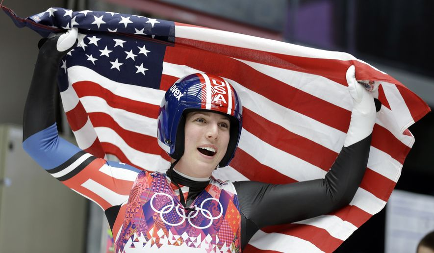 Erin Hamlin of the United States waves the flag after finishing her final run to win the bronze medalduring the women's singles luge competition at the 2014 Winter Olympics, Tuesday, Feb. 11, 2014, in Krasnaya Polyana, Russia. (AP Photo/Natacha Pisarenko)