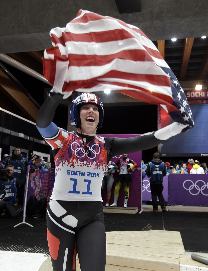 Erin Hamlin of the United States waves the flag to the crowd after finishing her final run to win the bronze medal during the women's singles luge competition at the 2014 Winter Olympics, Tuesday, Feb. 11, 2014, in Krasnaya Polyana, Russia.(AP Photo/Natacha Pisarenko)