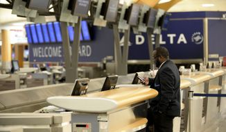 "Security employee Warren Johnson reviews messages at a nearly deserted Delta Air Lines counter after the carrier cancelled 573 flights into and out of Hartsfield-Jackson International Airport on Tuesday, Feb. 11, 2014 in Atlanta. The city dodged the first punch of a dangerous winter storm Tuesday, but forecasters warned of a potentially ""catastrophic"" second blow in a thick layer of ice that threatened to bring hundreds of thousands of power outages and leave people in their cold, dark homes for days.  (AP Photo/David Tulis)"