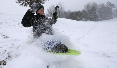 Stephen Clark, 12, hits a ramp made of snow near as he sleds near his home in Charlotte, N.C., Wednesday, Feb. 12, 2014, as a winter storm moves into the area. (AP Photo/Chuck Burton)