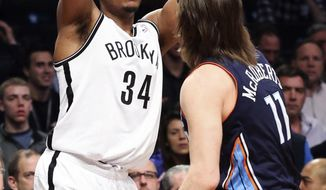 Brooklyn Nets forward Paul Pierce (34) looks to pass over Josh McRoberts in the first half of an NBA basketball game Wednesday, Feb. 12, 2014, in New York. (AP Photo/John Minchillo)