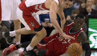 Toronto Raptors guard Greivis Vasquez, left, and Atlanta Hawks guard Dennis Schroder (17) battle for a loose ball during first-half NBA basketball game action in Toronto, Wednesday, Feb. 12, 2014. (AP Photo/The Canadian Press, Frank Gunn)