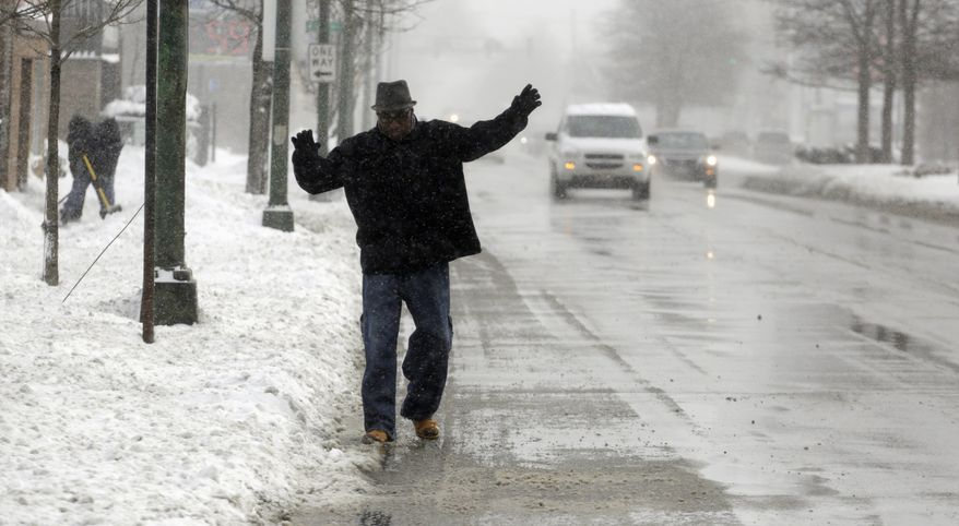 Easy does it: A commuter navigates a slippery street in Chicago. The National Weather Service says up to 6 inches of snow is expected in that area, along with 25 mph winds.