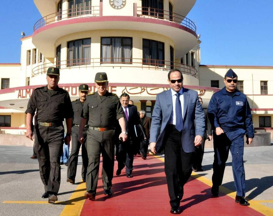 In this image released on the official Facebook page of the Egyptian Military Spokesman of the Armed Forces, Egyptian army chief Field Marshal Abdel-Fattah el-Sissi, second right, and Egypt's Foreign Minister Nabil Fahmy, center background, prepare to depart to Moscow from a military airport, in Cairo, Egypt, Wednesday, Feb. 12, 2014. El-Sissi headed to Moscow on Wednesday amid reports of a $2 billion arms deal in the making that would significantly expand Russia's military influence with a key U.S. ally in the Middle East. (AP Photo/The Official Facebook Page of the Egyptian Military Spokesman of the Armed Forces)