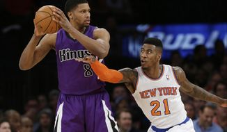 New York Knicks' Iman Shumpert (21) defends Sacramento Kings' Rudy Gay (8) during the first half of an NBA basketball game Wednesday, Feb. 12, 2014, in New York.  (AP Photo/Frank Franklin II)