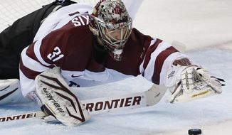 Latvia goaltender Edgars Masalskis dives for a puck in front of the net during the third period of the 2014 Winter Olympics men's ice hockey game against Switzerland at Shayba Arena, Wednesday, Feb. 12, 2014, in Sochi, Russia. (AP Photo/Petr David Josek)