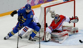 Sweden forward Nicklas Backstrom tries to wrap the puck around the goal against Czech Republic goaltender Jakub Kovar in the first period of a men's ice hockey game at the 2014 Winter Olympics, Wednesday, Feb. 12, 2014, in Sochi, Russia. (AP Photo/Julio Cortez)