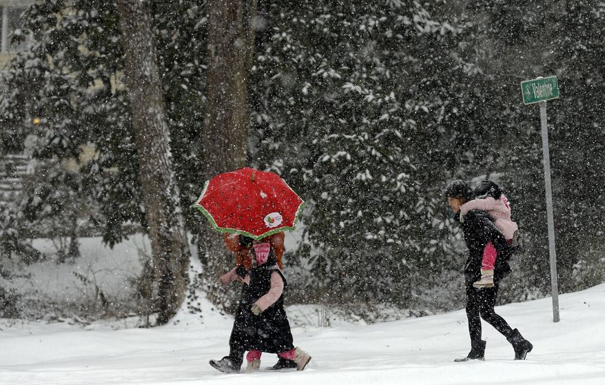 People maneuver a snow-covered street in Chapel Hill, N.C., Wednesday, Feb. 12, 2014. The National Weather Service has issued a winter storm warning for Wednesday and into Thursday covering most of North Carolina. (AP Photo/Gerry Broome)