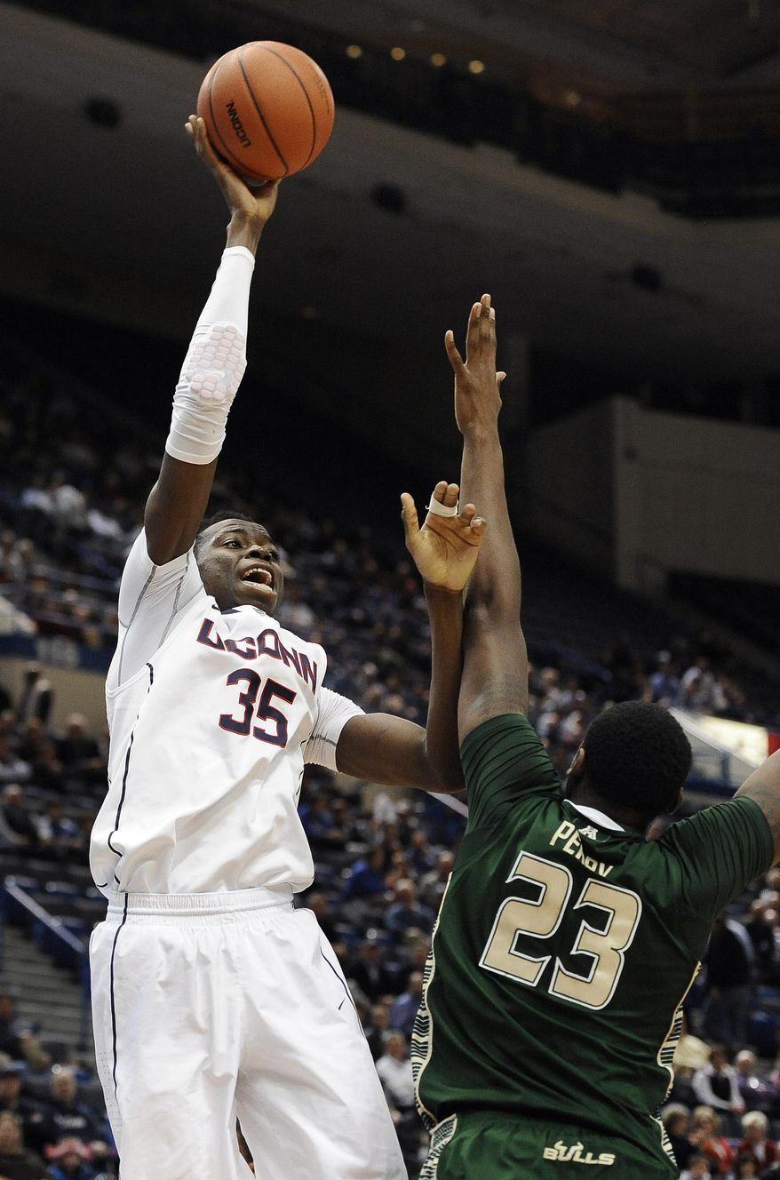 Connecticut's Amida Brimah, left, shoots over South Florida's Chris Perry, right, during the second half of an NCAA college basketball game on Wednesday, Feb. 12, 2014, in Hartford, Conn. Connecticut won 83-40. (AP Photo/Jessica Hill)